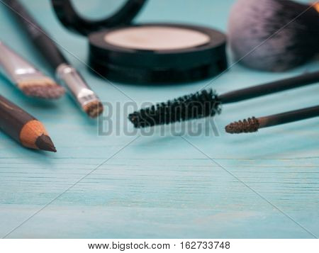 Blurred Set Of Makeup On Turquoise Wooden Background