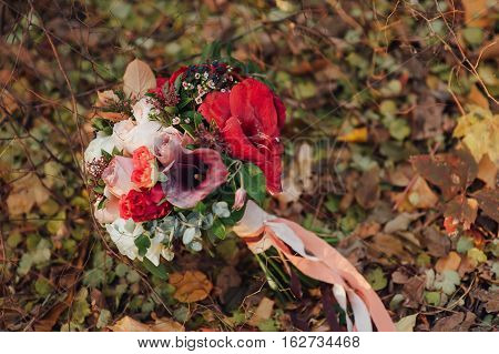 beautiful bridal bouquet of different flowers on yellow leaves