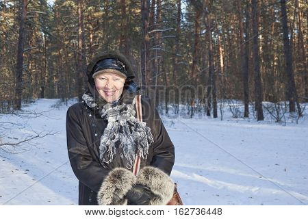 A woman of mature years smiling in sunny winter forest