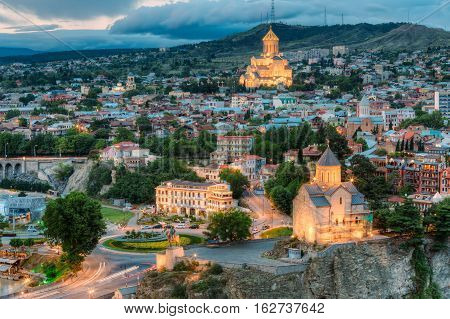 Evening View Of Tbilisi, Georgia. Summer Cityscape. On Photograph Visible Holy Trinity Cathedral Of Tbilisi And Metekhi Church