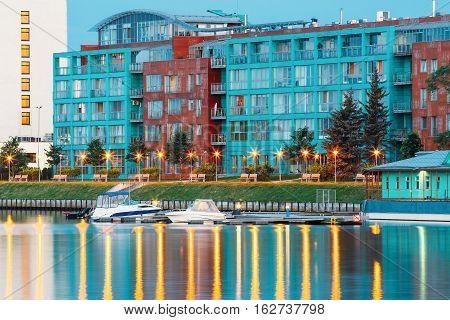 Riga, Latvia. Old Building At Evening Illuminated Embankment And Pier Of Daugava River In Summer Dusk.