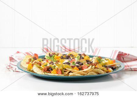 Delicious hot nachos on a green tin platter.