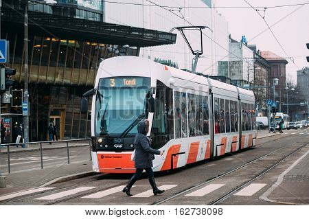 Tallinn, Estonia - December 2, 2016: Woman crossing road at a pedestrian crossing on tramways before staying tram.