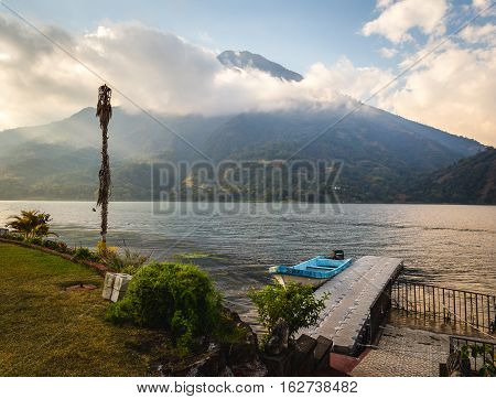 View on beach at Lake Atitlan, Guatemala, Central America. Clouds and blue sky over volcanic mountain. Dock in foreground.