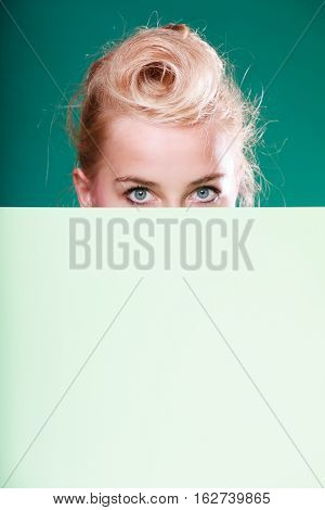 Woman standing behind white board at eye level half face only. Studio shot on blue green background