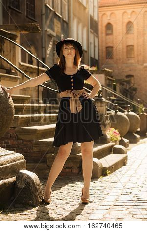 Portrait of young woman outdoors. Retro style fashion girl in black hat and dress on street of the old town european city Gdansk Danzig Poland