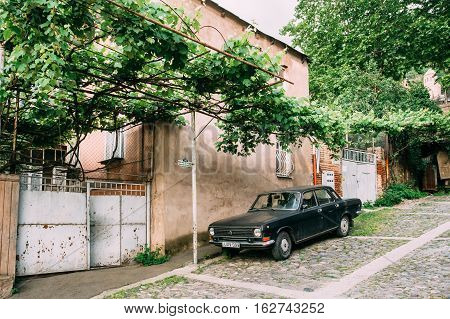 Tbilisi, Georgia - May 20, 2016: The View Of Parked Black Volga GAZ, Retro Rarity Car Near The Private Residential House Under Vine Canopy On Cobbled Green Street In Spring.