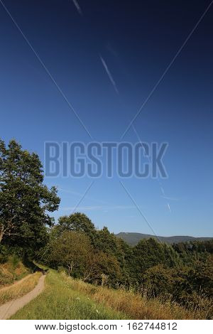 Beautiful landscape in Baden-Wurttemberg with diagonal vapor trail on blue sky.