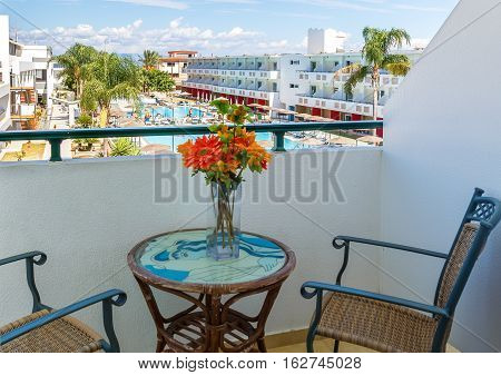 Balcony with chairs and table overlooking swimming pool at luxury tropical hotel