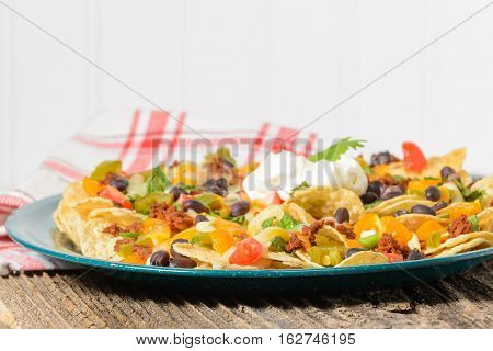 Plate of colorful nachos and cheese photographed closeup.