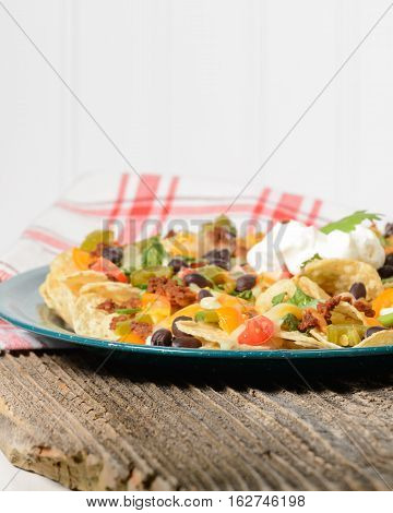 Plate of colorful nachos on a rustic wood table.