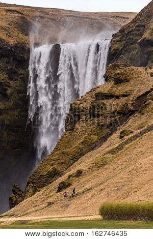Tourists are walking up the track at the Skogafoss waterfall where the water is blown upwards by strong wind in stormy weather