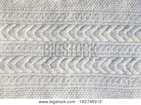 Beautiful white knitted pattern knitted scarf close up. Knitted background.