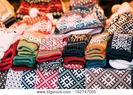 Close View Of Various Colorful Knitted Traditional European Warm Clothes - Caps Hats And Mittens At Winter Christmas Market. Souvenir From Europe.