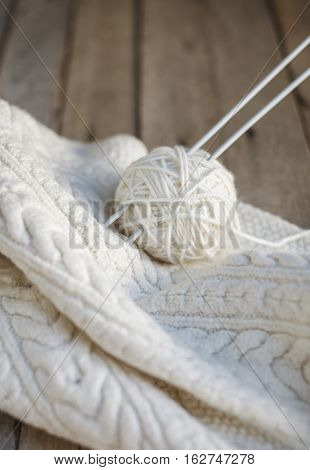Beautiful white knitting with needles. Hand-knitted scarf and ball of soft wool. Selective focus.