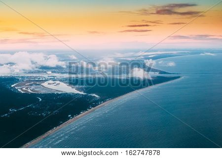Western Dvina Flows Into The Baltic Sea. River Divides The Northern And Kurzeme District Of Riga, Latvia. View From Airplane Window. Sunset Sunrise Over Gulf Of Riga, Bay Of Riga, Or Gulf Of Livonia