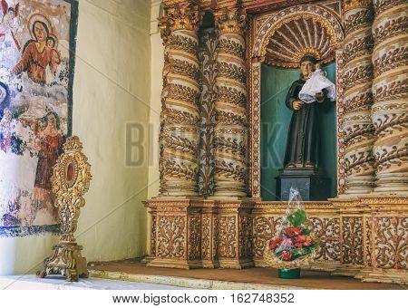 Old Goa, India - November 13, 2012: Interior of Basilica of Bom Jesus or Borea Jezuchi Bajilika - Roman Catholic church. Antique statue of Francis Xavier holding baby Jesus.