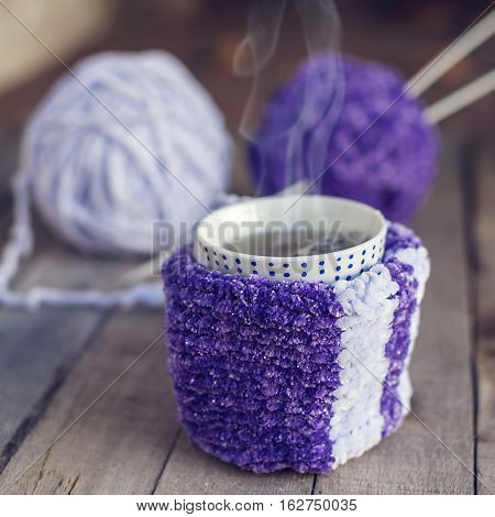 Cup of hot tea in knitted scarf with balls of yarn on the background. Hobbies.