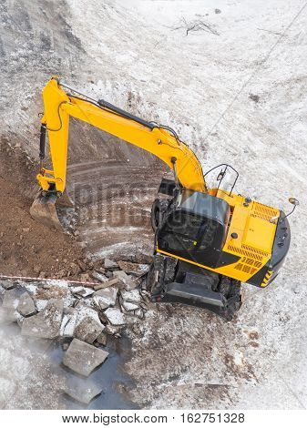 Excavators machine digging the ground in construction site constructing during winter top view