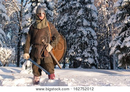 medieval warrior in winter forest in historical armor