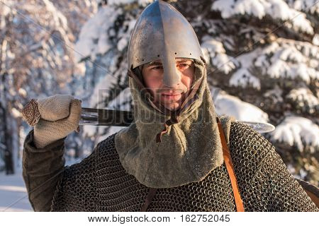 Portrait of medieval warrior in the winter forest in historical armor