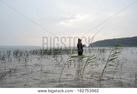 The fisherman stands in the water and catch fish on the bait. Weather rainy and Vatan. On the water is visible wave and splashes of rain.