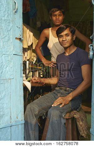 MANDU, MADHYA PRADESH, INDIA - NOVEMBER 19, 2008: Two young men at work in the tailor shop in the rural hilltop town of Mandu in Madhya Pradesh, India.
