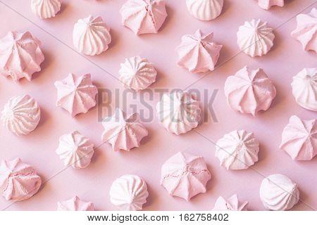 Pink tender meringues on pink paper background