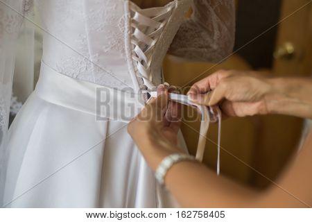 tighten white wedding dress on bride, wedding gown
