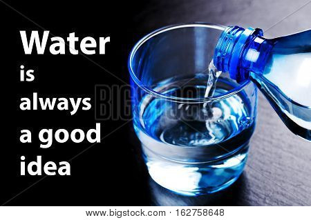 Water flowing from a plastic bottle into a glass. Water is always a good idea