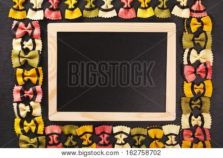 Farfalle tigrate pasta forming frame on dark stone background. Place for text in a black chalkboard. Concept of slow carbohydrates for healthy nutrithion.
