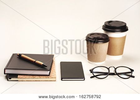 Notebook, coffee to go, smart phone, pen and eye glasses are lying on grey background. Stuff for office worker or businessmen, top view. Place for your logo.
