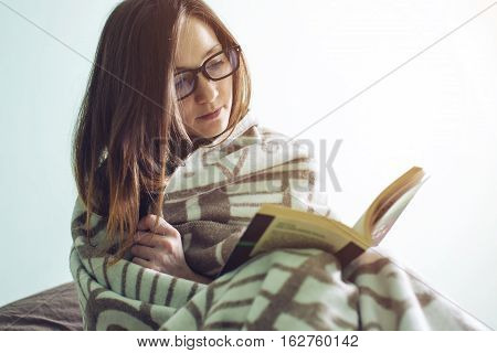 Woman Wrapped In A Warm Blanket Reading Book