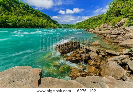Gorgeous amazing beautiful stunning view of Niagara Falls escarpment rushing river and grounds on sunny summer day