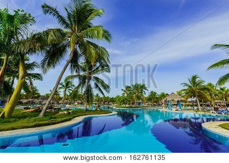 Holguing Province, Playa Pesquero Hotel, Cuba, Aug. 31, 2016, amazing beautiful inviting of stylish swimming pool  in tropical garden on sunny gorgeous day