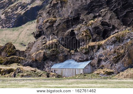 Shed of the Drangshlid farm built into the large odd-shaped rock Drangurinn, South Iceland