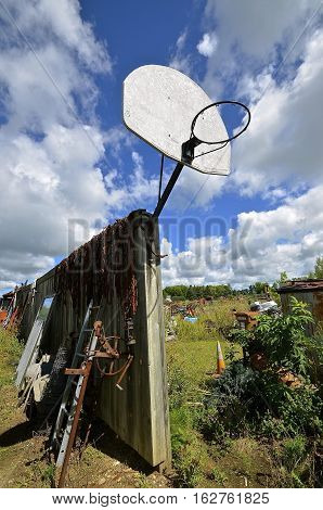 An old basketball backboard and rim are attached to a fence in a junkyard