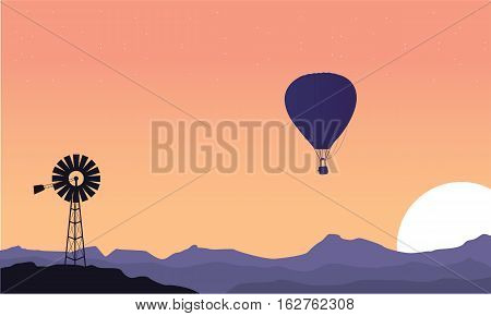 Silhouette of windmill and air balloon scenery vector art