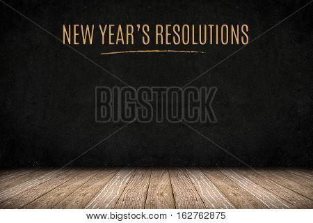 New Year's Resolutions Gold Text On Blackboard Wall On Wood Plank Floor,new Year Business Presentati
