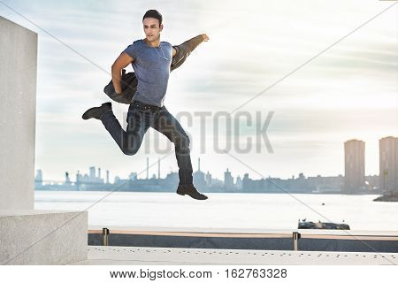 Handsome young adult man having fun and jumping in the city wearing leather jacket gray t-shirt and jeans.