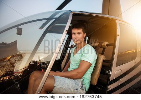 Young handsome man sitting in helicopter cockpit. Private helicopter pilot ready to fly in city on a bright sunny day.