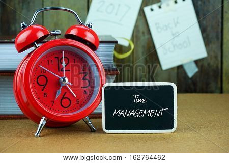 Business or education inscription written on black chalkboard. Alarm clock, books, pen, spectacle and notes on brown table desk.