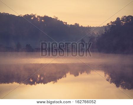 Landscape at lake before the sun rises with mist on the water