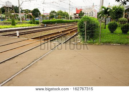railway track with tree and bush on side taken in bogor station indonesia java