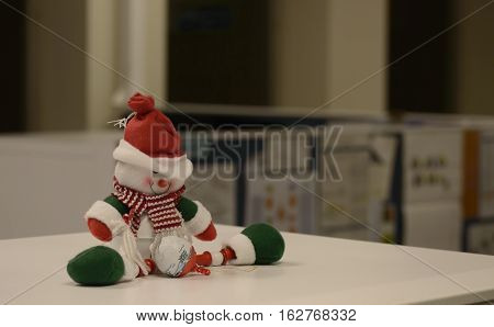 Cute Office Cubicle Christmas Work Background with copy space for message and Employee Decorations A snowman sitting on top of cubicle with hat tilted down after hours when office is closed for HR to write message or sign