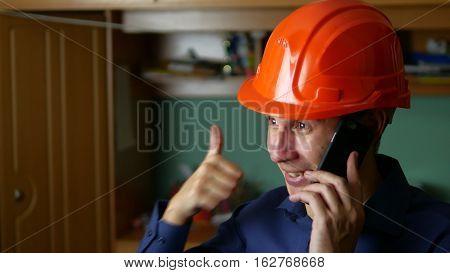 man construction worker in hard hat talking phone smartphone indoor
