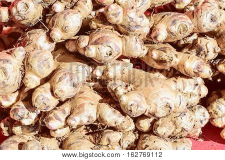 Fresh ginger at a market stall. Selective focus of ginger in a wooden