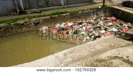 Mound of trash clogs a dirty river photo taken in Bogor Indonesia java
