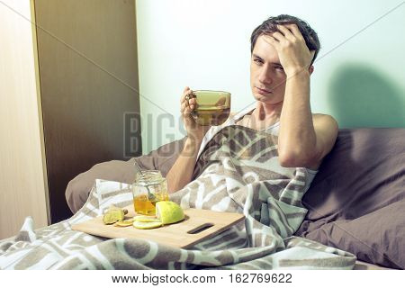 Young Man Lies In Bed Sick With Colds And Flu