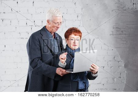 Old people hold a laptop and communicate through the Internet. Happy smiling grandpa grandma couple standing cuddling together isolated on white brick background
